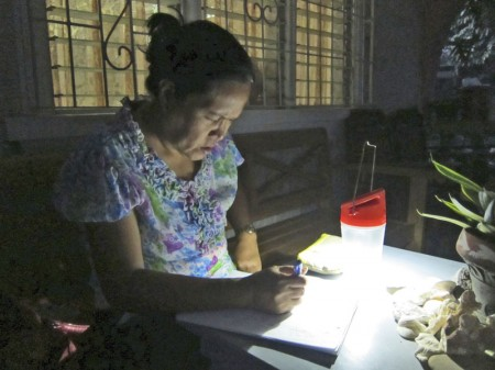 A woman using the affordable solar power lantern.